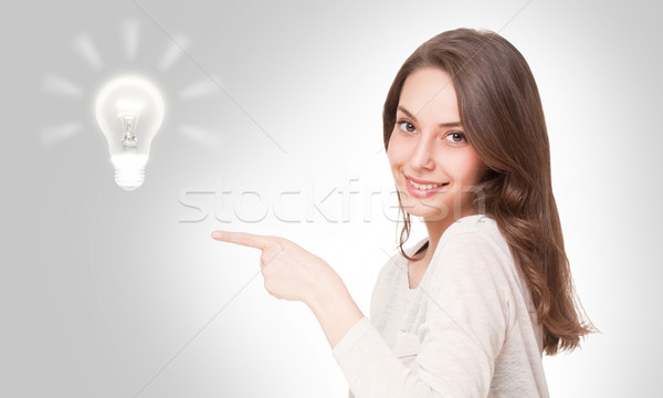 Young brunette beauty with light bulb symbol. Stock photo © lithian
