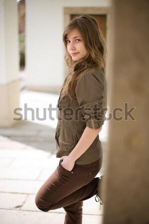Stock photo: Beautiful young brunette posing outdoors.