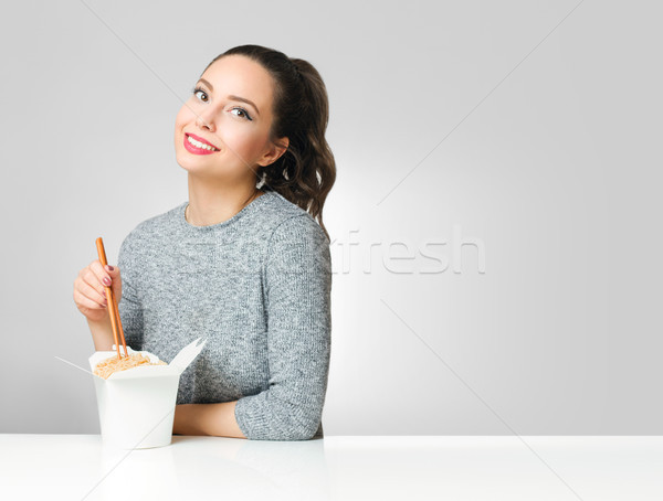 Cute brunette eating asian food. Stock photo © lithian