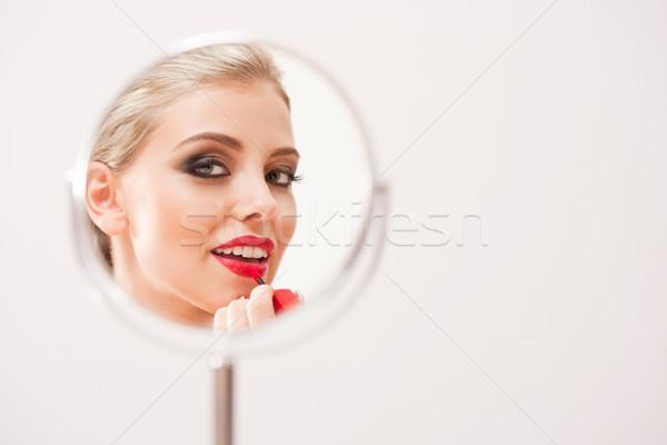 Blond beauty putting on makeup. Stock photo © lithian