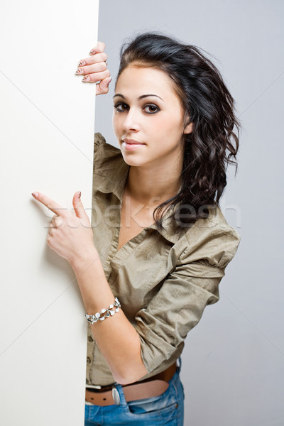 Attractive young brunette holding blank billboard. Stock photo © lithian
