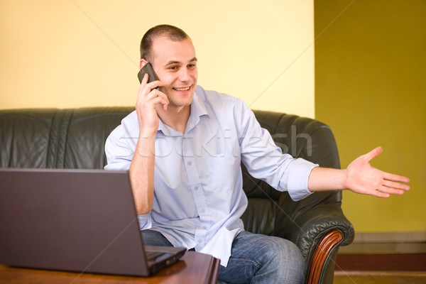 Young businessman communictaing with cellphone. Stock photo © lithian