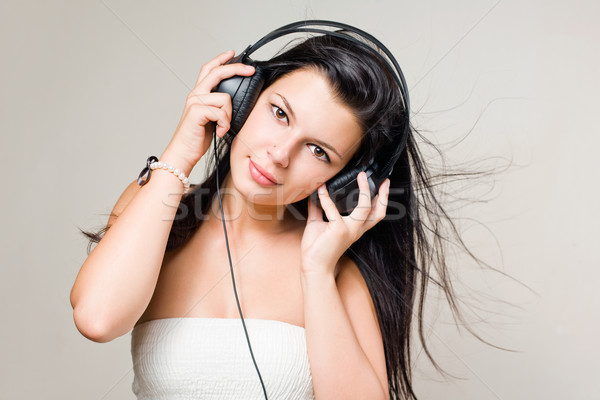 Feliz morena ouvir música fones de ouvido Foto stock © lithian
