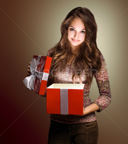Beautiful brunette peeking inside gift box. Stock photo © lithian