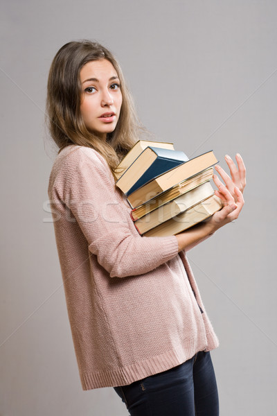 Young brunette with large pile of books. Stock photo © lithian
