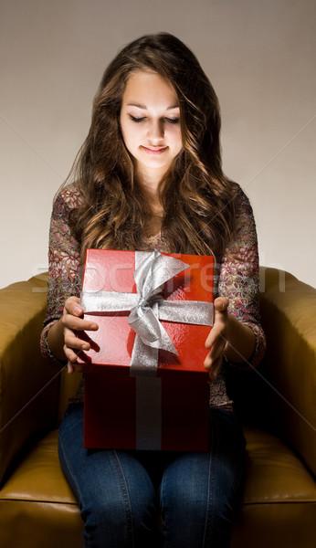 Beautiful brunette peeking inside gift box. Stock photo © lithian