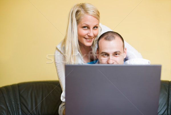 Young couple peeking over laptop screen Stock photo © lithian