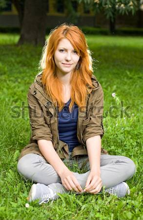 Romantic portrait of a young redhead girl sitting in the park. Stock photo © lithian