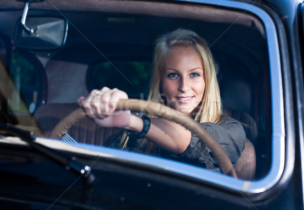 Beautiful young blond girl  in a black vintage car. Stock photo © lithian