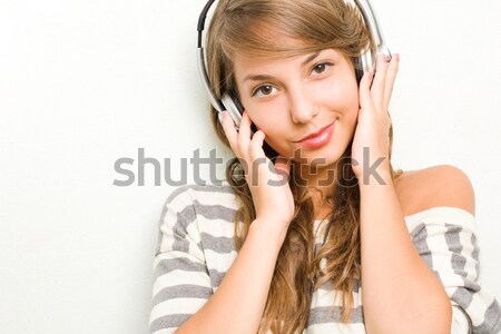 Beautiful young brunette listening to music with headphones. Stock photo © lithian
