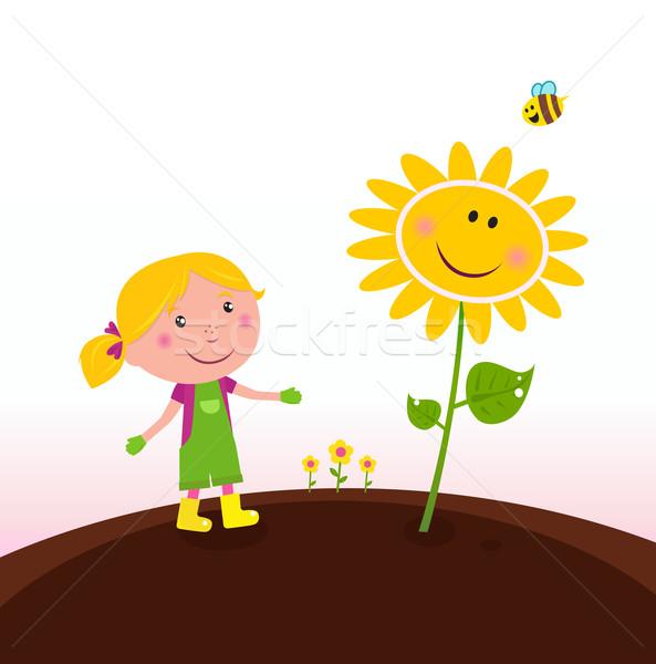 Spring gardening : Gardener child with sunflower in the garden  Stock photo © lordalea
