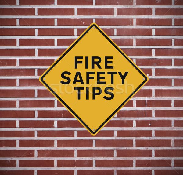 Fogo segurança dicas placa sinalizadora parede parede de tijolos Foto stock © lorenzodelacosta