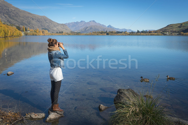 woman is standing and using binoculars  Stock photo © lostation