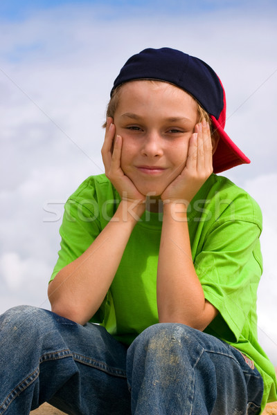 Smiling boy relaxing head in hands Stock photo © lovleah