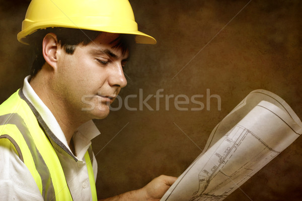 Male builder site foreman reading architectural industrial plans Stock photo © lovleah