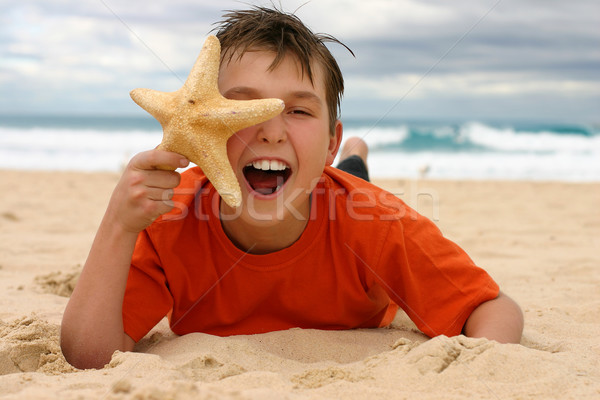 Laughing boy with starfish on the beach Stock photo © lovleah