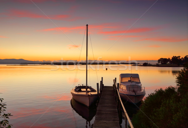 Boats moored to jetty at sunrise Stock photo © lovleah