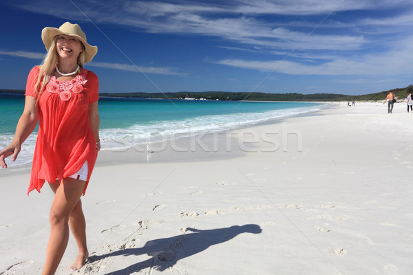 Happy smiling woman walking along beautiful sandy beach Stock photo © lovleah