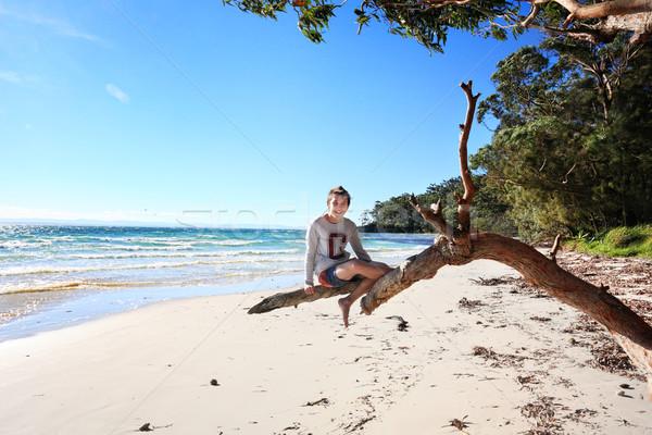 Cheerful teen boy sitting on tree  holiday at the beach Australi Stock photo © lovleah