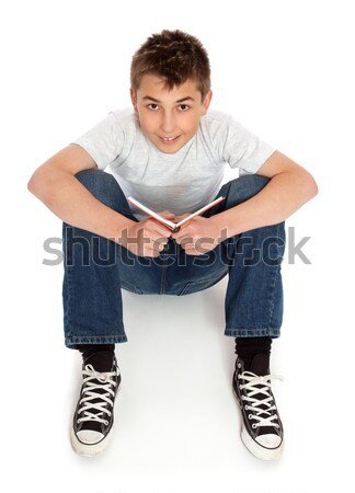 Pre teen boy sitting in jeans and t-shirt Stock photo © lovleah