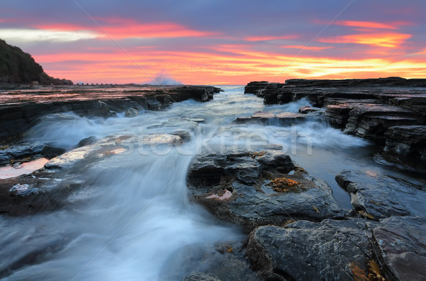 Sunrise waves flowing into rock chasm seascape Stock photo © lovleah