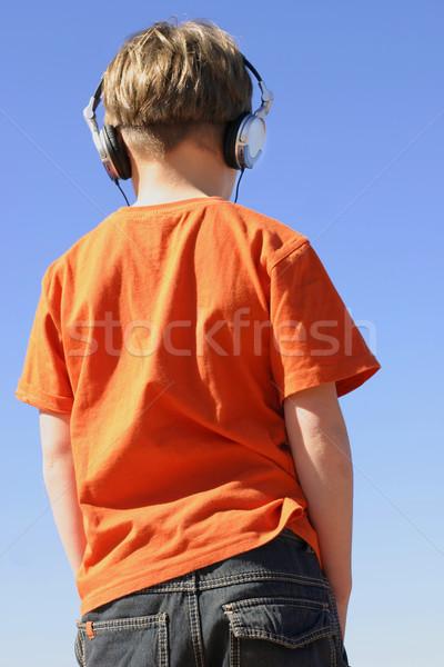 Młodzieży słuchania muzyki słuchawki młody chłopak dżinsy Zdjęcia stock © lovleah