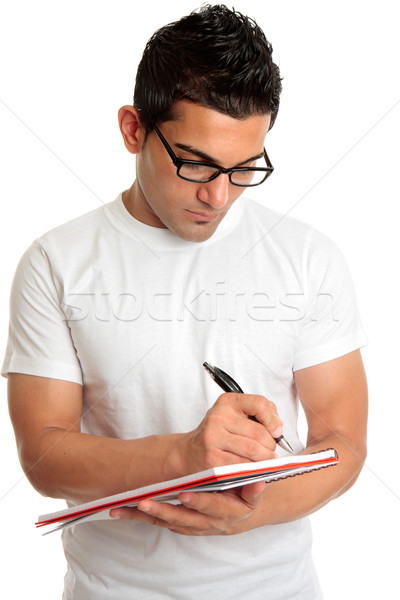 Student in glasses writes in book Stock photo © lovleah