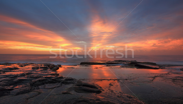 Streaks of orange red light at sunrise Curl Curl Stock photo © lovleah