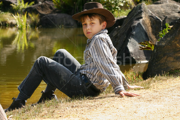 Rural boy sitting by banks of a river Stock photo © lovleah