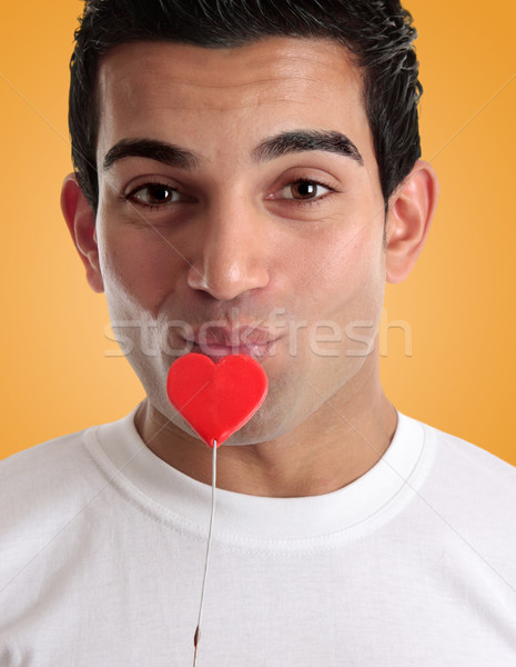Amorous man kissing love heart on a stick Stock photo © lovleah