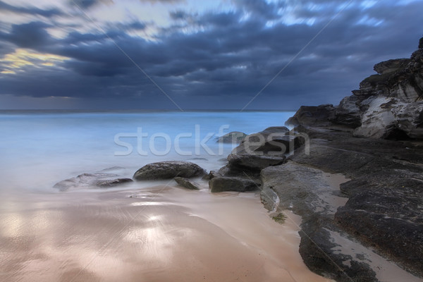 Stunning beach and coastal rocks before sunrise Stock photo © lovleah