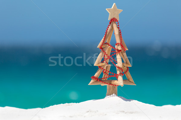 Driftwood Christmas tree decorated with string of red baubles at Stock photo © lovleah