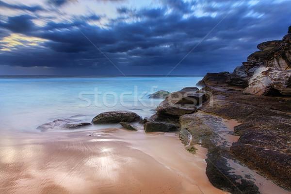 Stunning beach and coastal rocks before sunrise Stock photo © lovleah