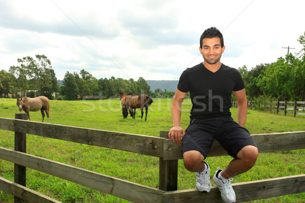 man sitting on th efence of a horse paddock Stock photo © lovleah