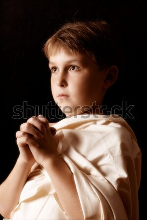 Young boy in plain robe pleading or praying Stock photo © lovleah