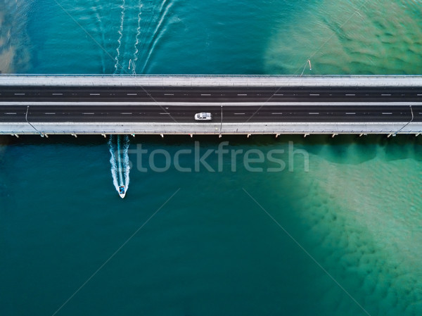 Car crosses bridge as speed boat travels under it. Aerial view Stock photo © lovleah
