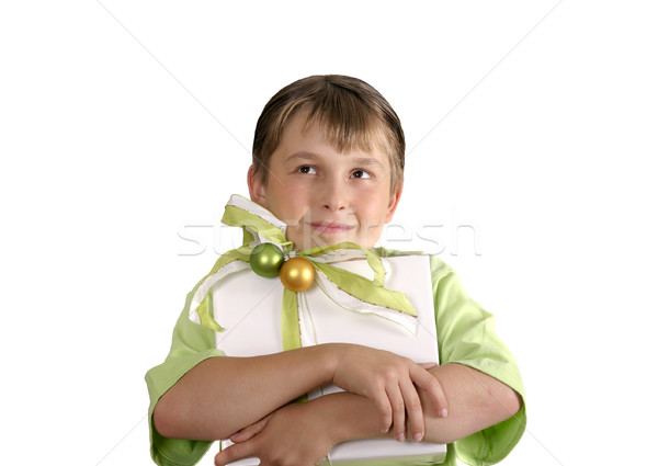 Stock photo: Child holding a wrapped present and thoughtfully looking up