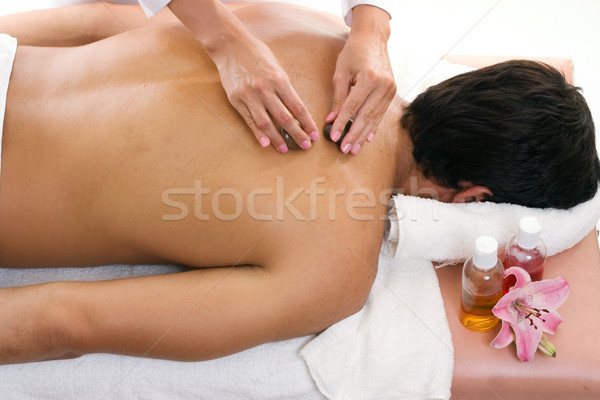 Man receiving thermal stone massage Stock photo © lovleah