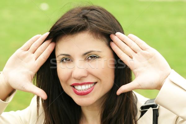 Gülen kadın eller yüz güzel esmer Stok fotoğraf © lovleah