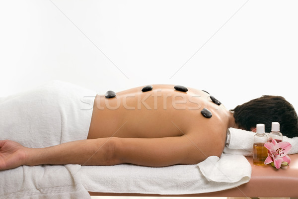 Male enjoys thermal stone spa treatment Stock photo © lovleah