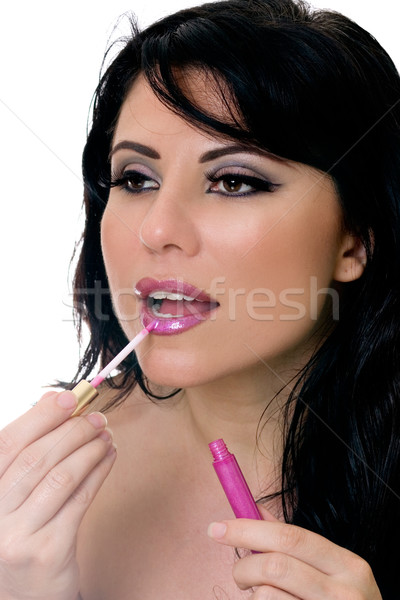 Pretty attractive woman applying lip gloss to lps Stock photo © lovleah