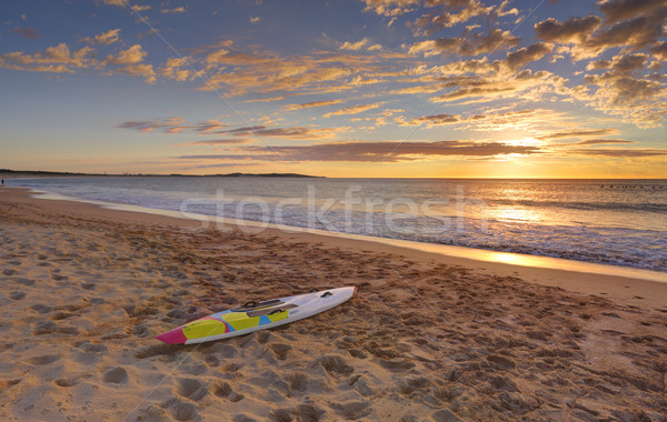 Stock photo: Beach sunrise and paddleboard on shoreline