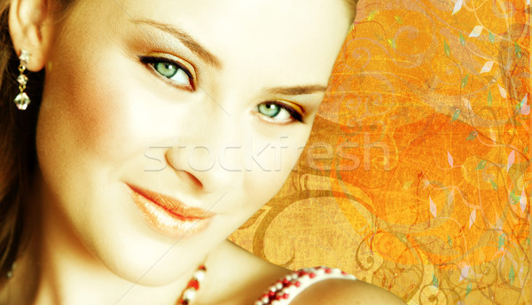 Stock photo: woman's face close-up on grunge background