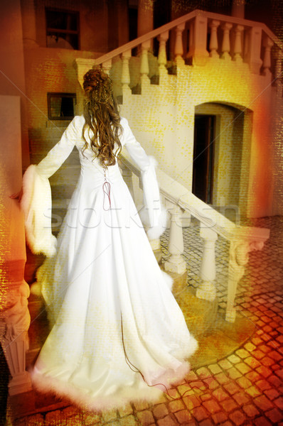 beautiful bride in long silk coat on staircase Stock photo © lubavnel
