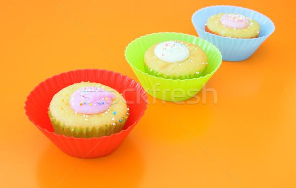 Three vanilla muffins in plastic cups Stock photo © lubavnel