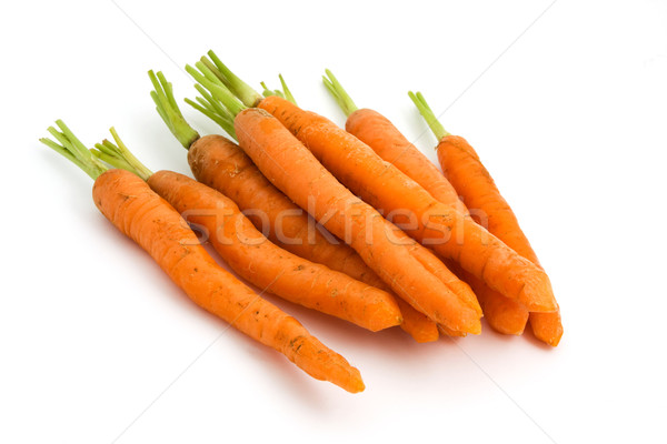 Pile of organic carrots with green tops over white Stock photo © lucielang