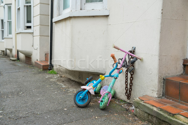 Stock photo: Two childrens scooters chained up in a street