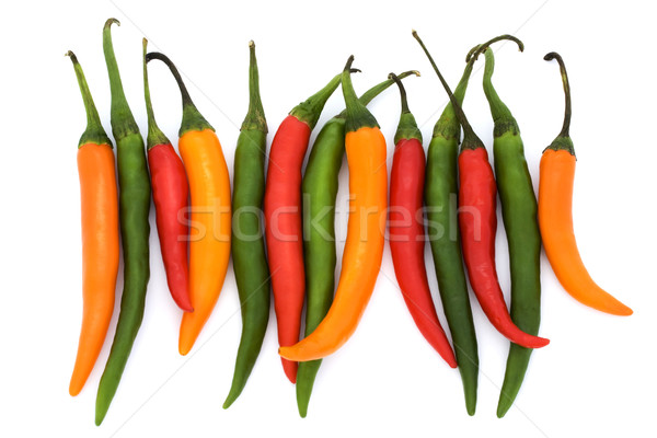 Red, green and yellow chillies in a line over white. Stock photo © lucielang