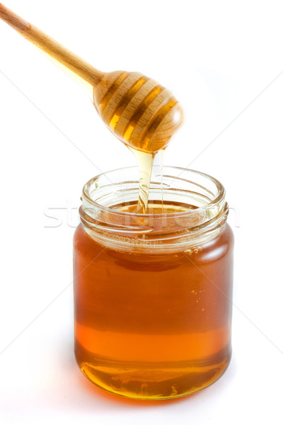Honey dripping into jar over white Stock photo © lucielang