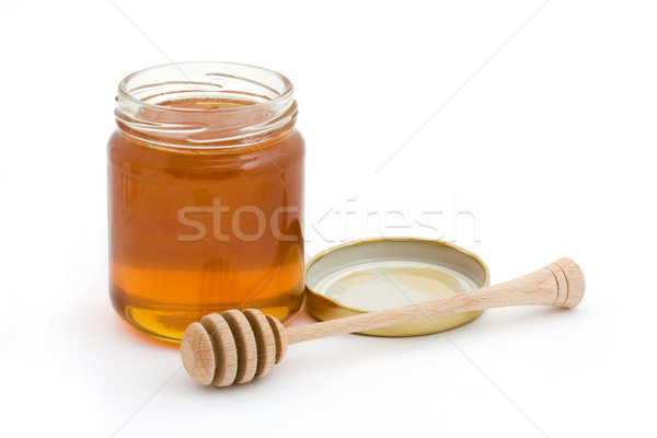 Jar of open honey with wooden drizzler Stock photo © lucielang